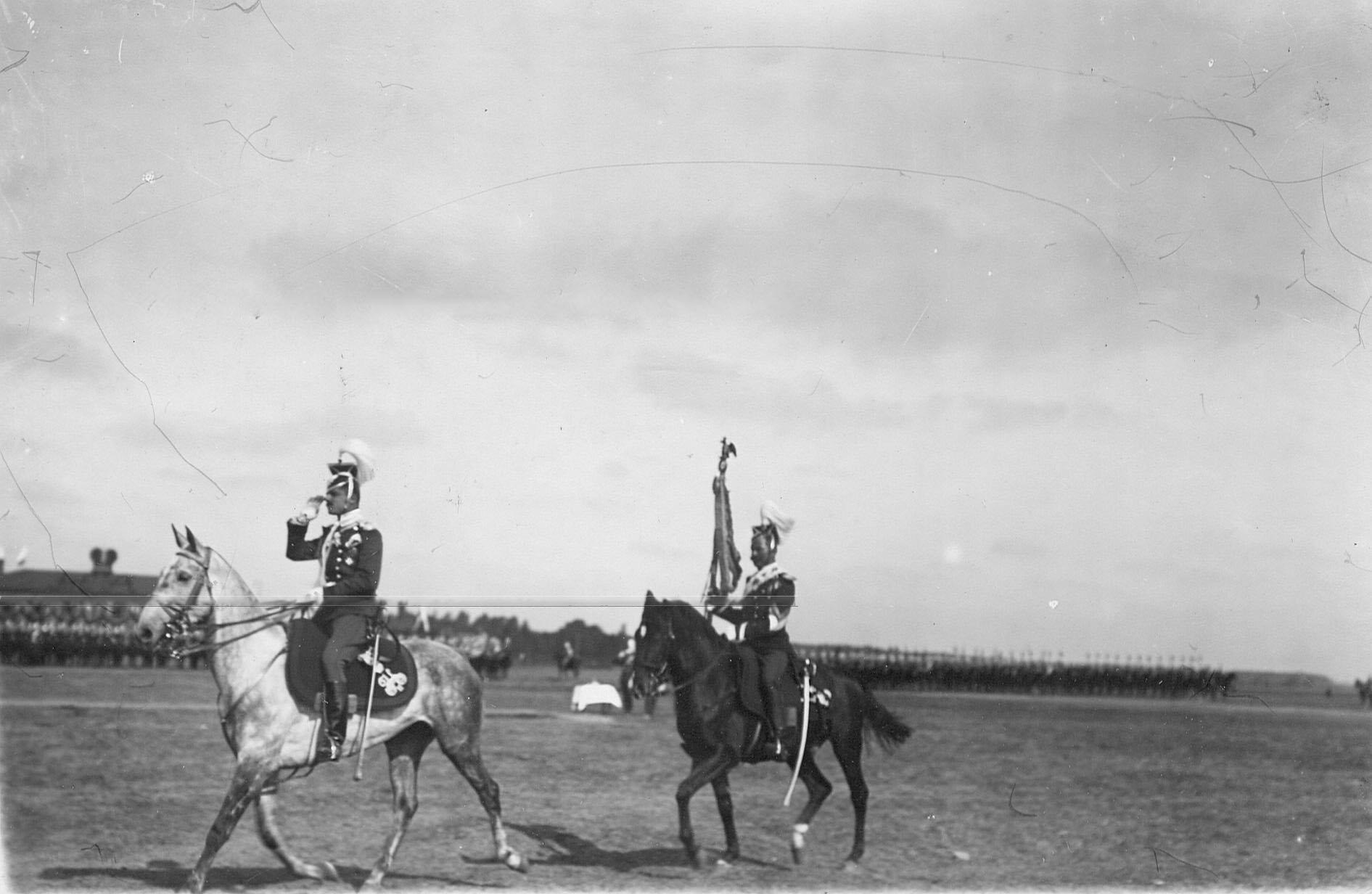 Адъютант полка князь Эристов и штандартный унтер-офицер объезжают выстроившихся для парада улан в день празднования 250-летнего юбилея полка