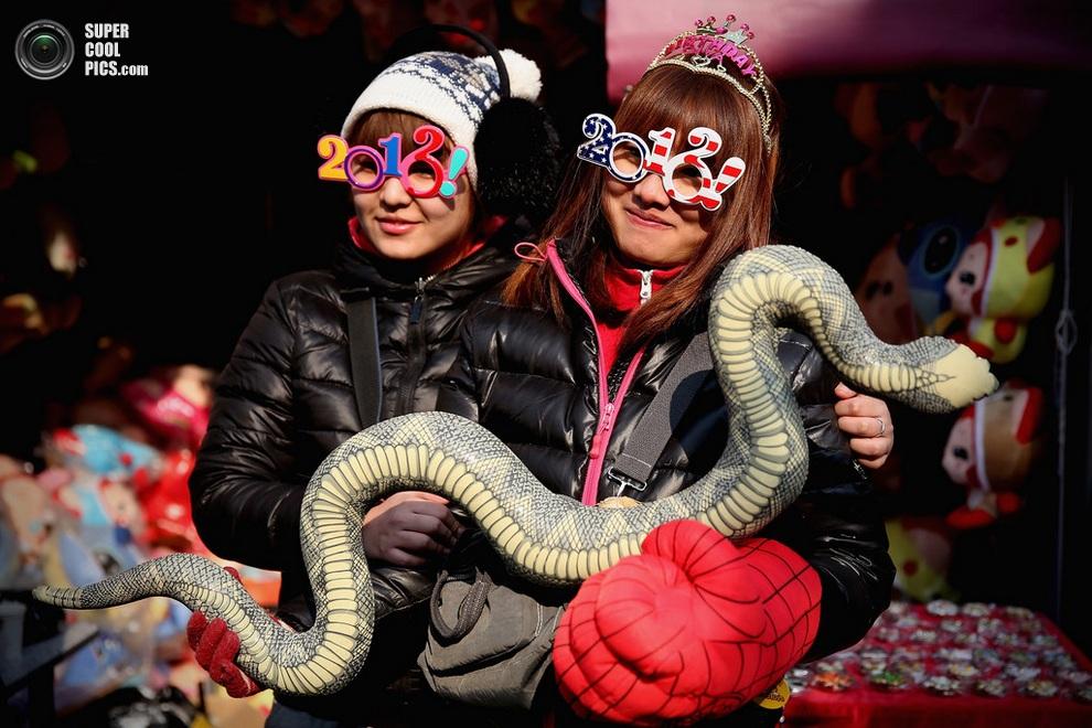 Китаянки с игрушечнойзмейкой—символом наступившего года. (Feng Li/Getty Images)