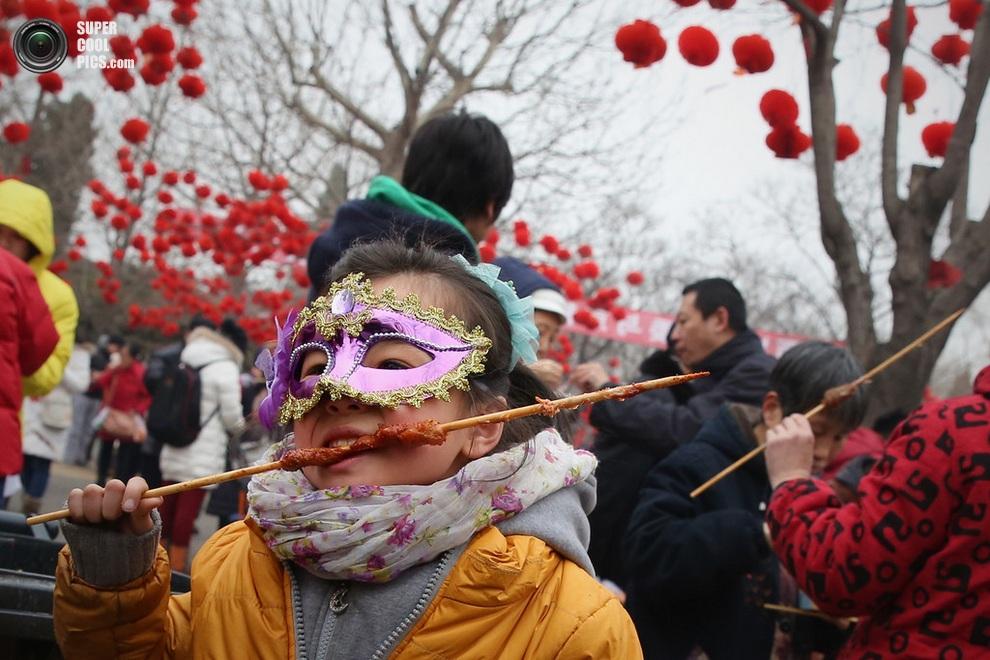 Китайская девочка доедает шашлычок во время празднования Нового года. (Feng Li/Getty Images)