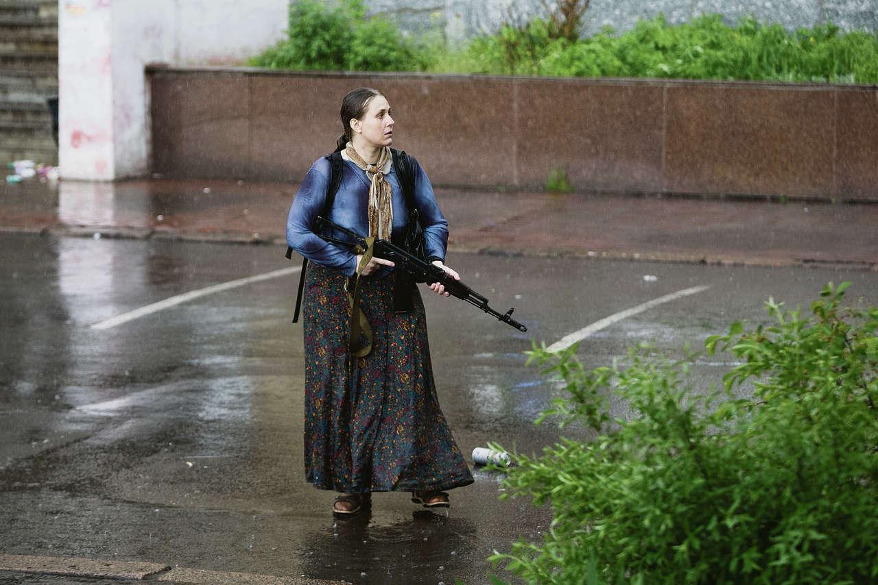 Женщина с автоматом занимает позицию во время грозы в центре Славянска