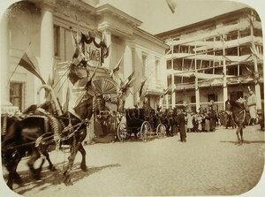Чиновники, военные и горожане приветствуют членов императорской фамилии, выходящих из кареты.