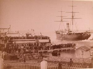 Местные жители на пристани встречают прибывающее судно.