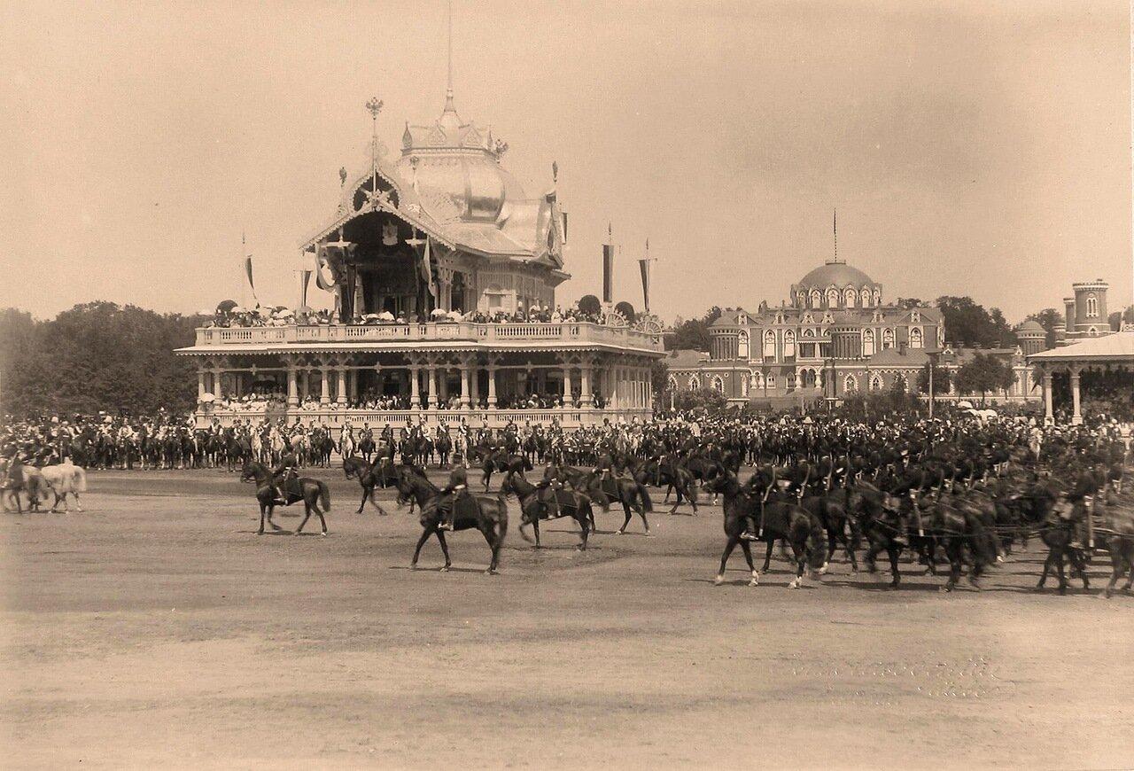 Прохождение артиллерийских частей церемониальным маршем во время парада на Ходынском поле; в центре - императорский павильон, справа - Петровский путевой (подъездной) дворец