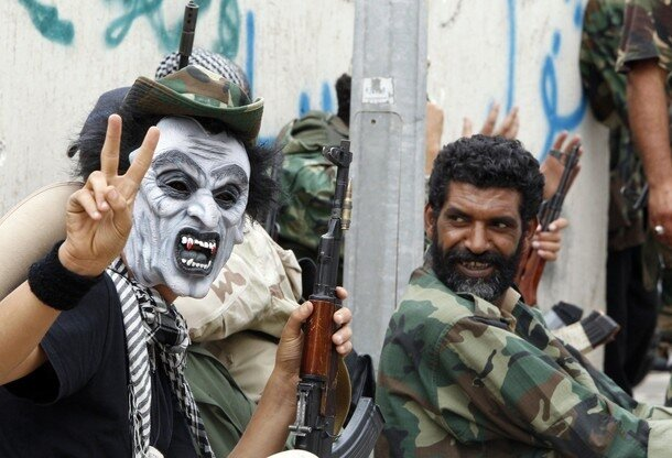 A mask-wearing rebel fighter loyal to Libya's interim government flashes a victory sign in Sirte