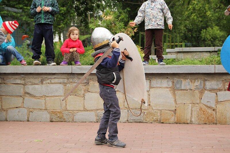Маленький мальчик в средневековых доспехах, которые ему велики