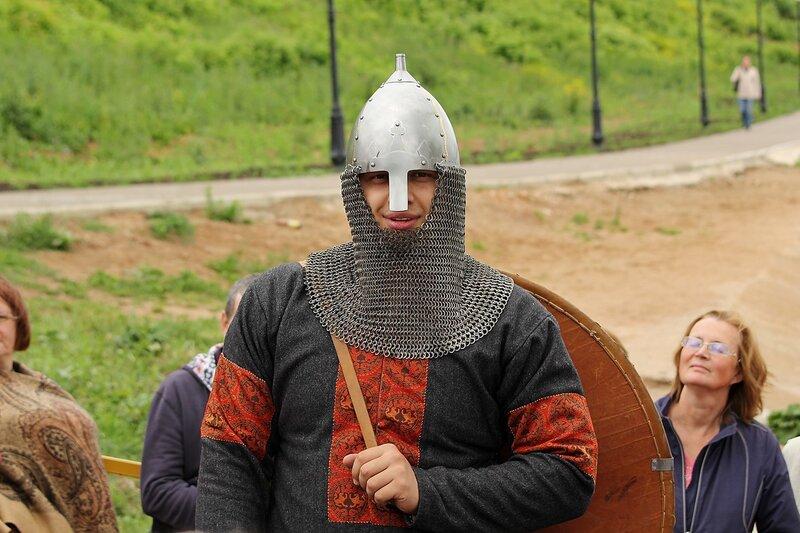 реконструктор в одежде и доспехах 11 века: шлем с кольчужной защитой и щит из досок, обитый кожей