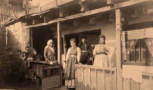 Семья крымских караимов в национальных костюмах у входа в дом.