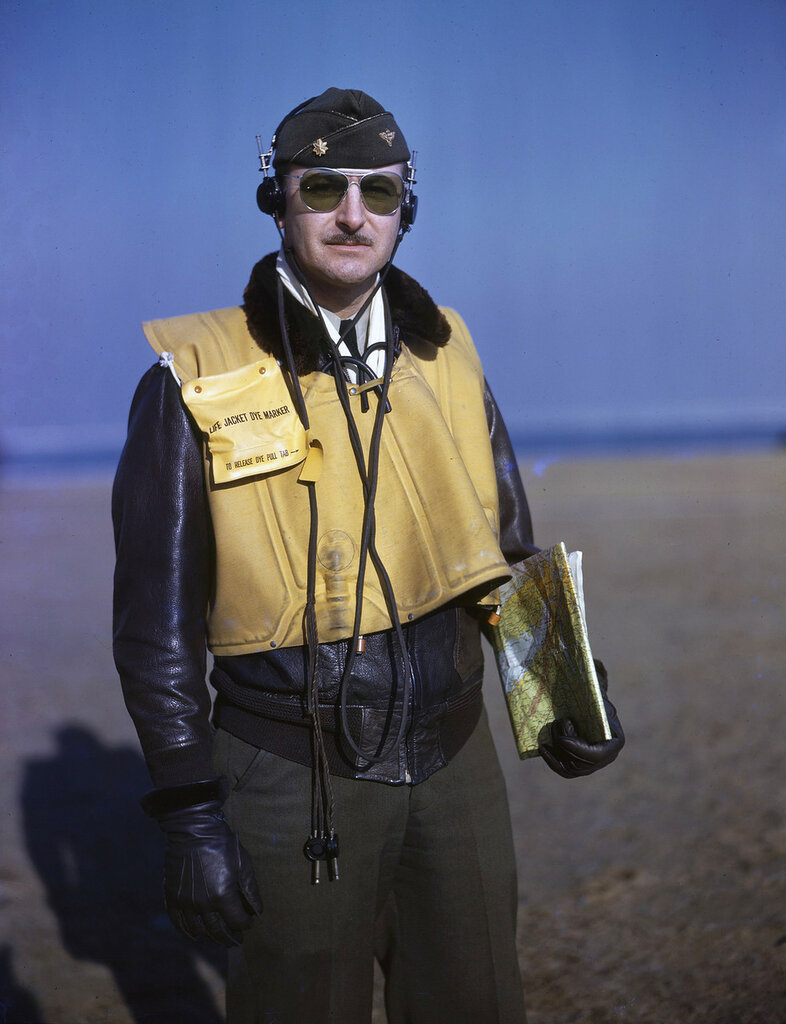 U. S. Coast Guard Lt. Commander E.J. Suydam in flight clothing, wearing headphones, carrying map, wearing yellow life jacket and dye marker, 1943.