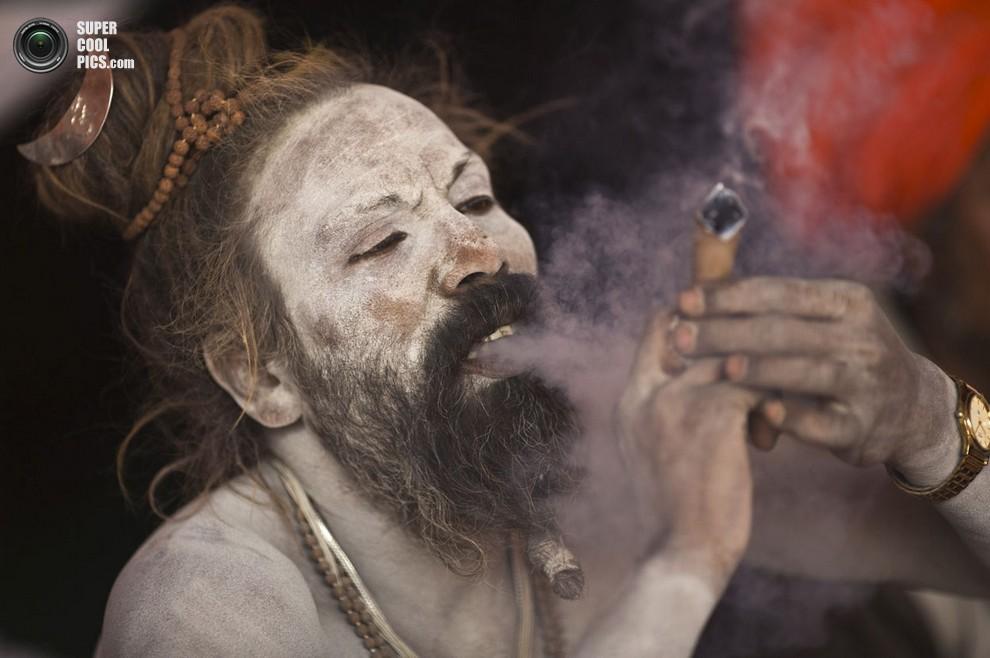Садху курит марихуану на берегу реки Ганг накануне фестиваля. (REUTERS/Ahmad Masood)