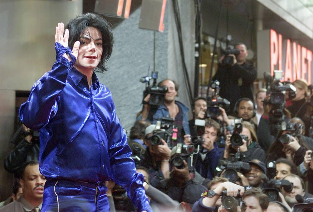 Майкл Джексон позирует перед фотографами на презентации своего альбома Invincible на Таймс-сквер в Н