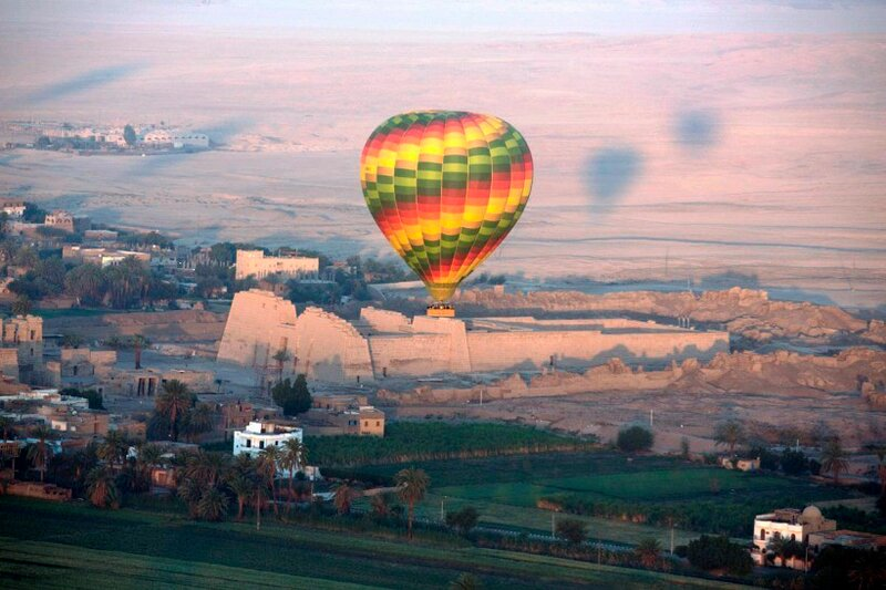 Воздушный шар летит над храмом Рамзеса III в Мединет Хабу на западном берегу реки Нил в Луксоре, Египет. Только с воздушного шара, поднявшись высоко в небо в чистом воздухе раннего утра, туристы могут понять красоту древностей этой столицы Древнего Египта когда-то известной, как Фивы.