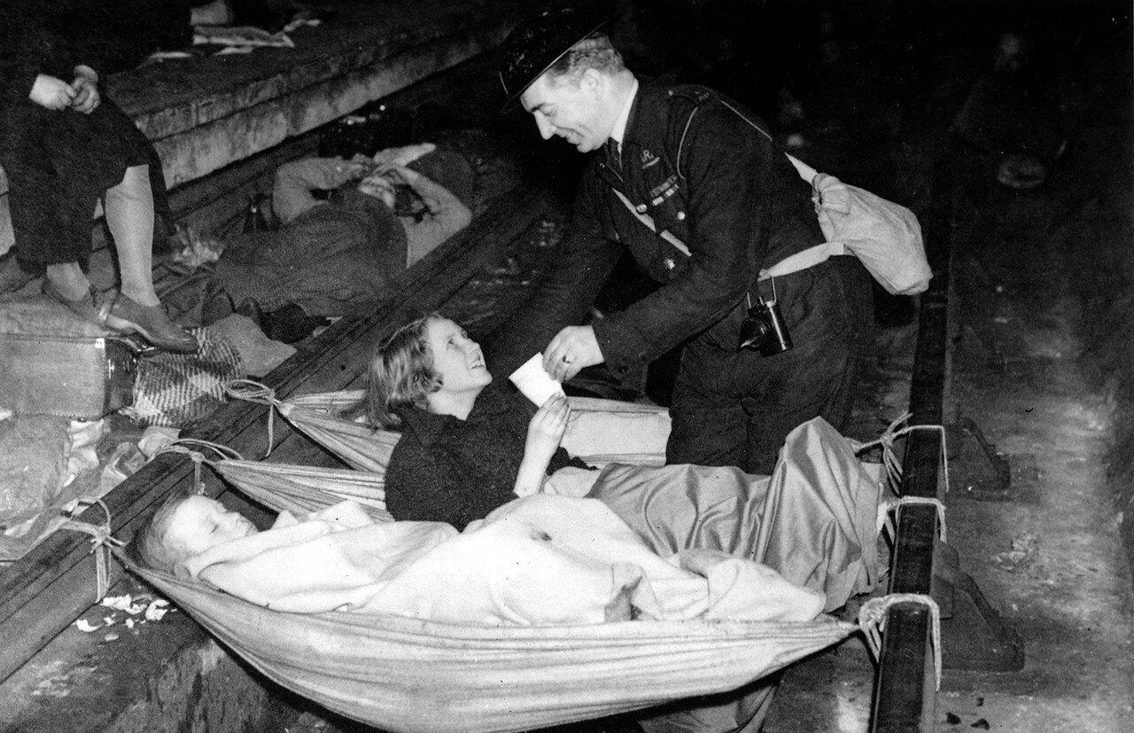 1940. Во время воздушного налета смотритель приносит стакан воды для молодой девушки, проснувшейся в бомбоубежище на станции «Олдвич». 21 октября