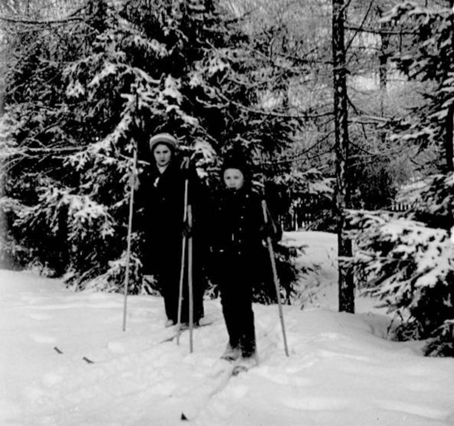Женщина и ребенок на лыжах в лесу