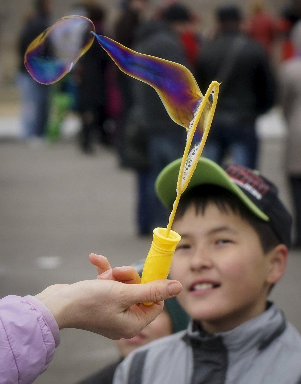 A boy looks on as a woman makes soap bubbles during a celebration to mark Maslenitsa, or Pancake Week, in Baikonur, Kazakhstan