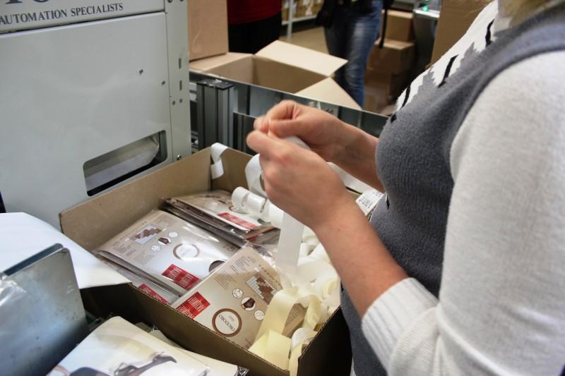 20. а еще один сотрудник наклеивает стикеры с маркировкой цвета и размера.