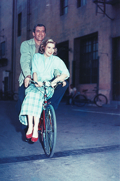 James Stewart and Grace Kelly, cycling through the studio lot during the filming of Rear Window (1954).jpg