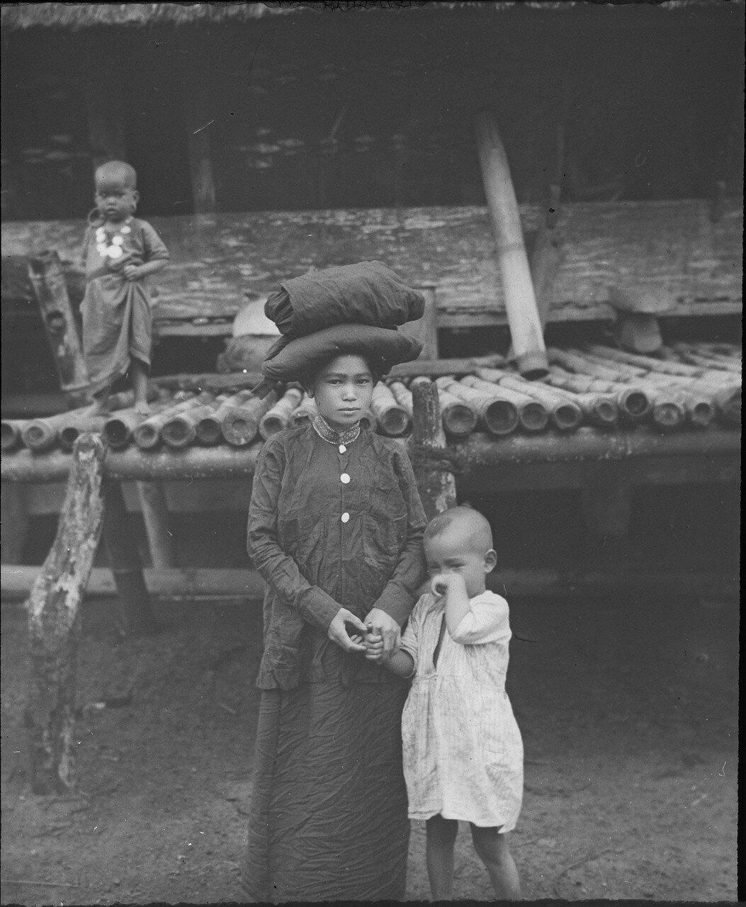 Женщина народности каро с головным убором и ребенком