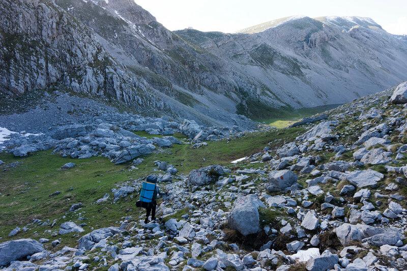 турист с рюкзаком спускается с перевала под горой Астрака