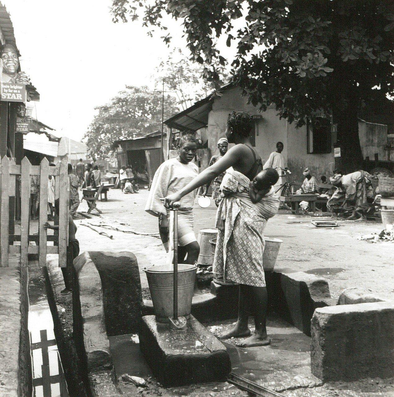 Городские окраины. Нигерийские женщины у водонапорной колонки