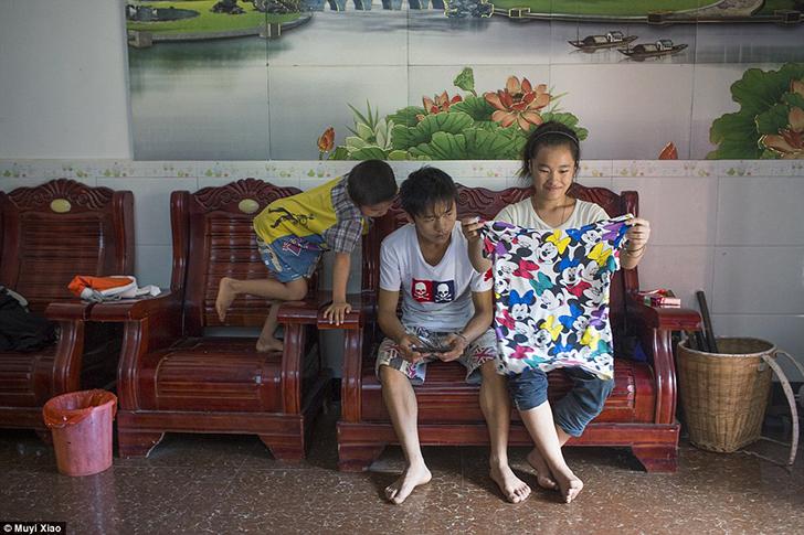 Сяо Ли разглядывает футболку, а ее 19-летний муж Сяо Минь играет в игры на мобильном телефоне рядом