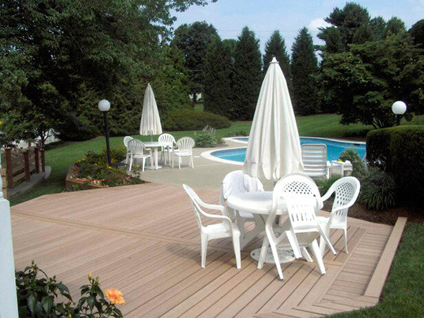 Deck in this back yard landscape design with poolside seating with white chairs and table and umbrella.