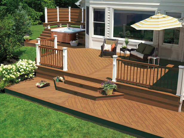 Multi level deck design in this backyard space with shaded seating area, railing, steps leading to yard, and hot tub on the side of the home.