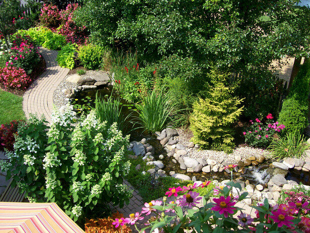Wide view of a colorful garden, stream, pond, trees, plants, and walkway. This beautiful garden is featured on Rate My Space.