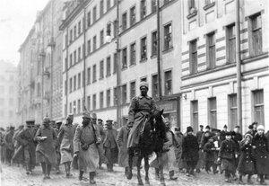 Военнопленные, окруженные любопытными, проходят под конвоем по одной из улиц города