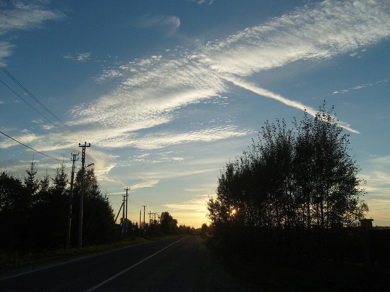 облака и инверсионные следы на предзакатном небе