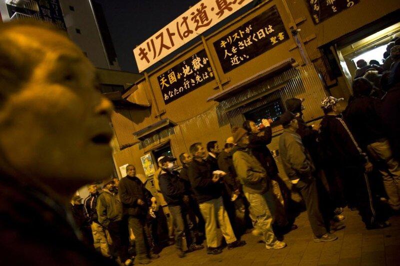 Люди стоят в очереди, чтобы получить бесплатную еду в церкви 17 января 2009 года в Осаке