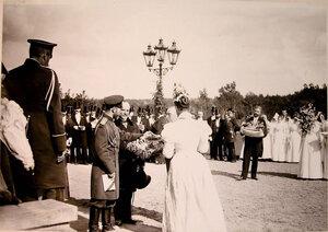 Представители местной власти и воспитанницы женского института преподносят цветы императору Николаю II и императрице Александре Федоровне.