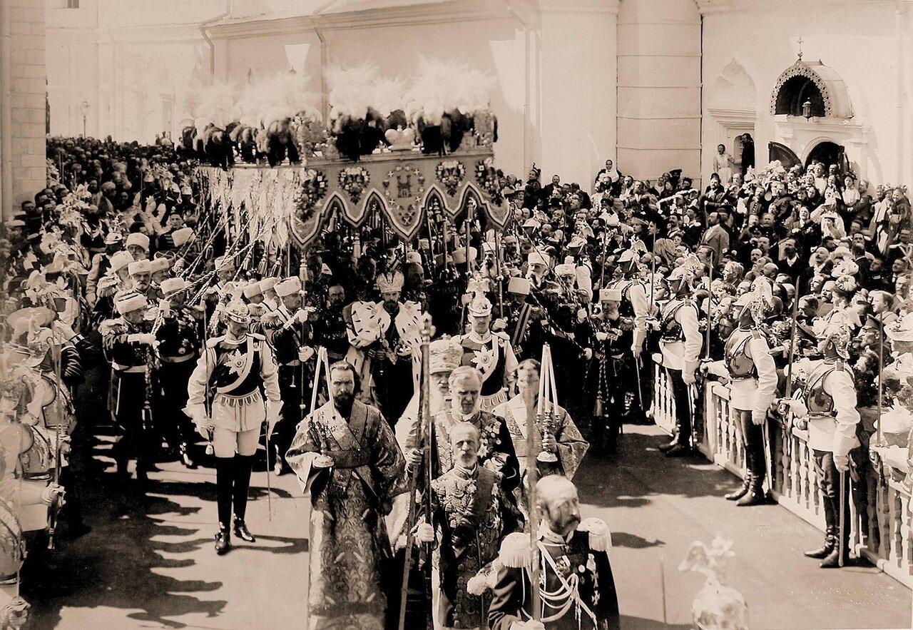 Торжественное шествие императора Николая II (под балдахином) в сопровождении свиты по окончании церемонии коронации в Успенском соборе Кремля; справа на первом плане - церемониймейстеры (с жезлами)