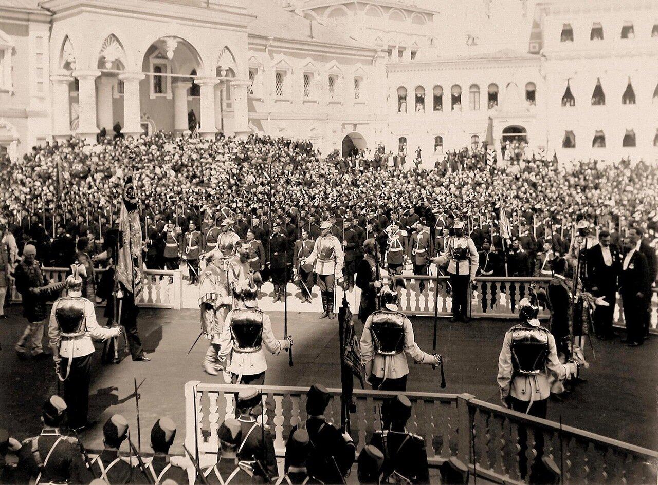 Церемониймейстеры (с жезлами) и герольды проходят мимо Чудова монастыря в Кремле в день торжественной коронации; справа на втором плане - вид части фасада Малого Николаевского дворца