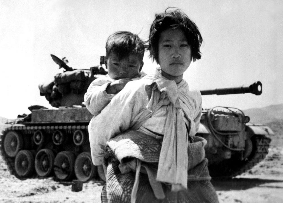 Уставшие после долгого пути девочка с братом на фоне танка M-26, Хэнгджу, Корея, 9 июня 1951 года. (U.S. NavyMaj. R.V. Spencer, UAF).jpg
