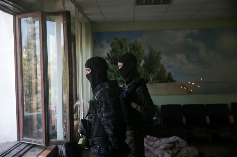 Pro-Russian masked men stand watch inside the Mariupol town hall in east Ukraine