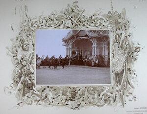 Император Николай II (в центре первый на коне), императрица Александра Федоровна (стоит в павильоне) и сопровождающие их военные чины после объезда войск перед смотром.