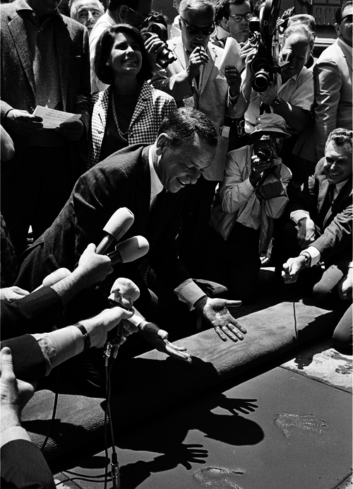 Frank Sinatra places his hands and feet in the cement at Grauman's Chinese Theatre on July 20th, 1965.png