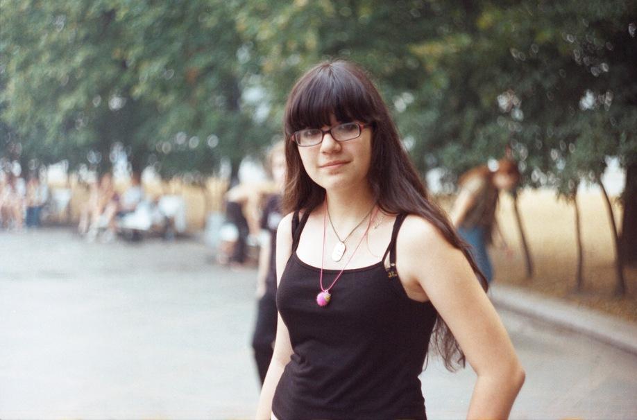 Девушка в чёрной майке, очках и с жетоном.