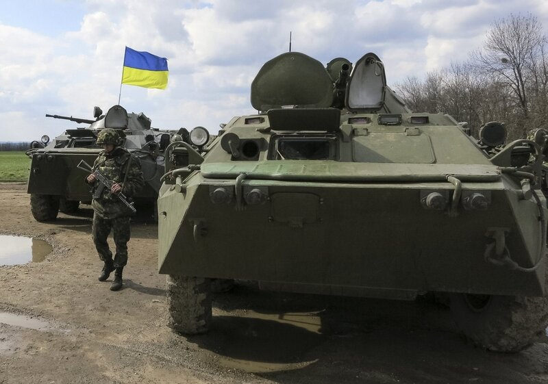 A Ukrainian soldier is seen near armored personnel carriers at a checkpoint near the town of Izium