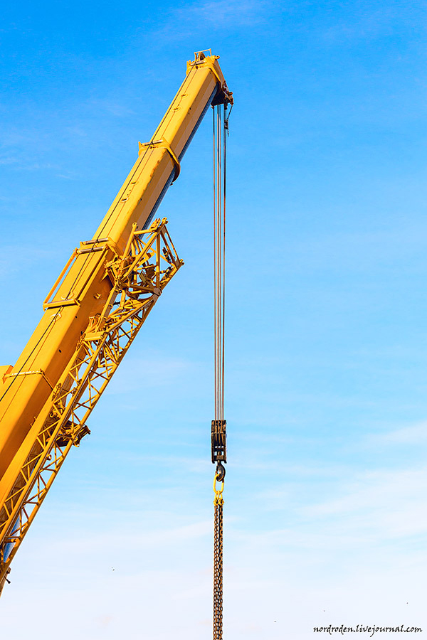 Yellow boom of the crane against the blue sky.