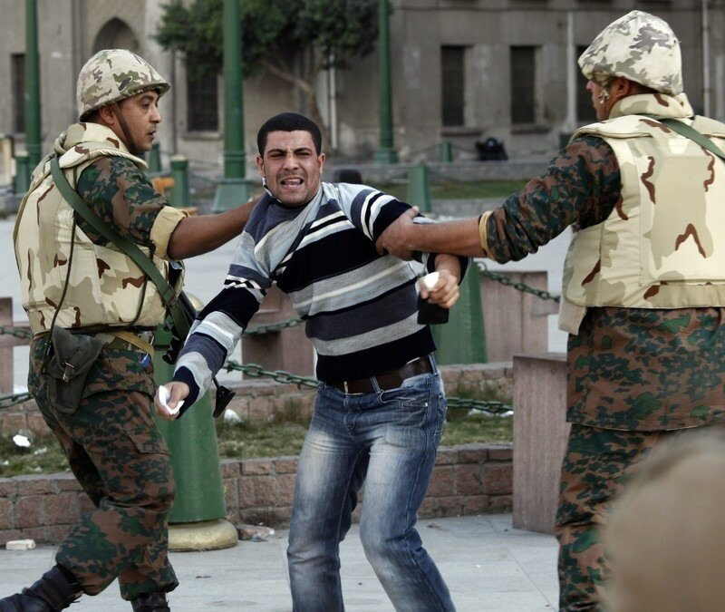 A pro-Mubarak protester captured by anti-government demonstrators is handed over to the army during clashes at Tahrir Square in Cairo