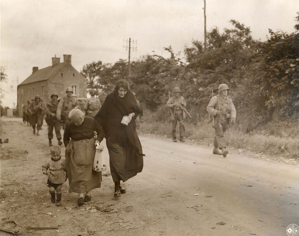 Collection Rodger Hamilton: The War Photoshttp://wosu.org/2012/archive/hamilton/gallery.php?page=gallery1Refugees leaving town.Deux vieilles femmes et un jeune enfant parmi une unité US qui progresse à la sortie d'un village dans le bocage.Au moin