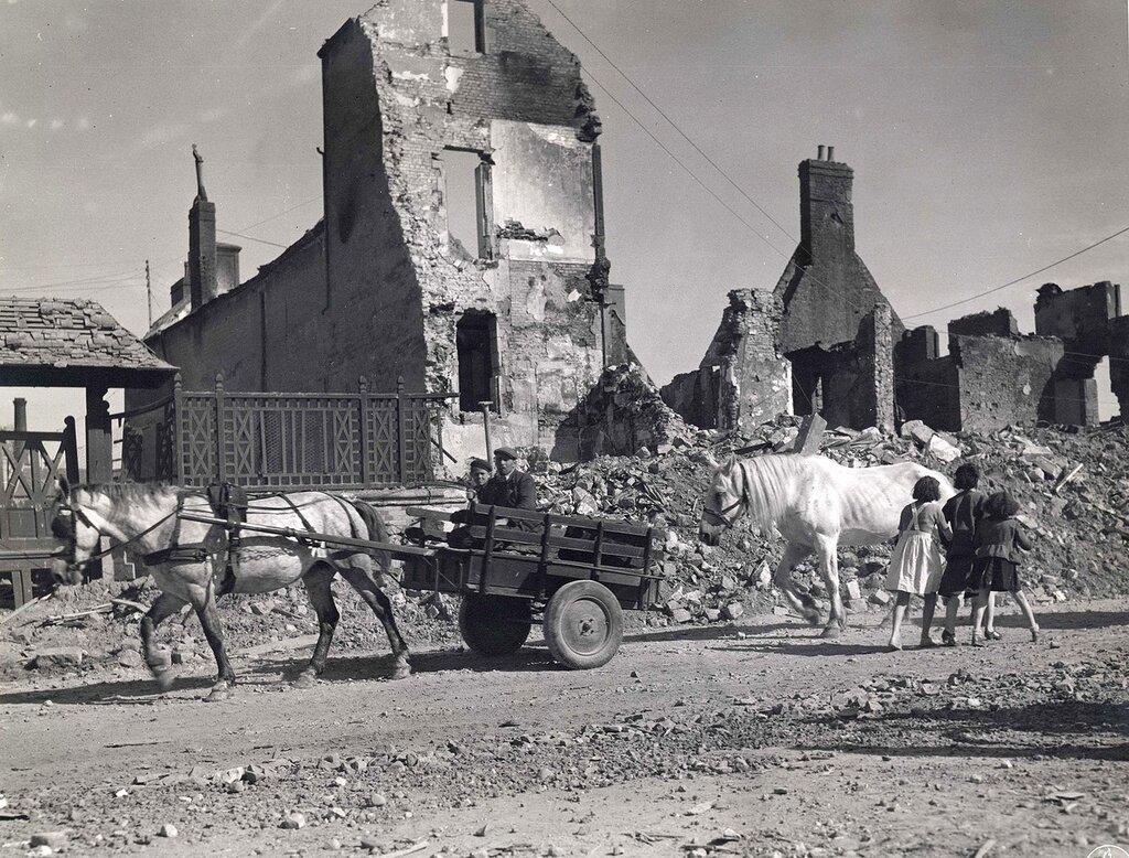 Collection Rodger Hamilton: The War Photoshttp://wosu.org/2012/archive/hamilton/gallery.php?page=gallery1Civils au milieu des ruines d'Isigny sur Mer (Calvados).  Deux d'entre eux sont en attelage, suivis par un second cheval et croisent une femme a