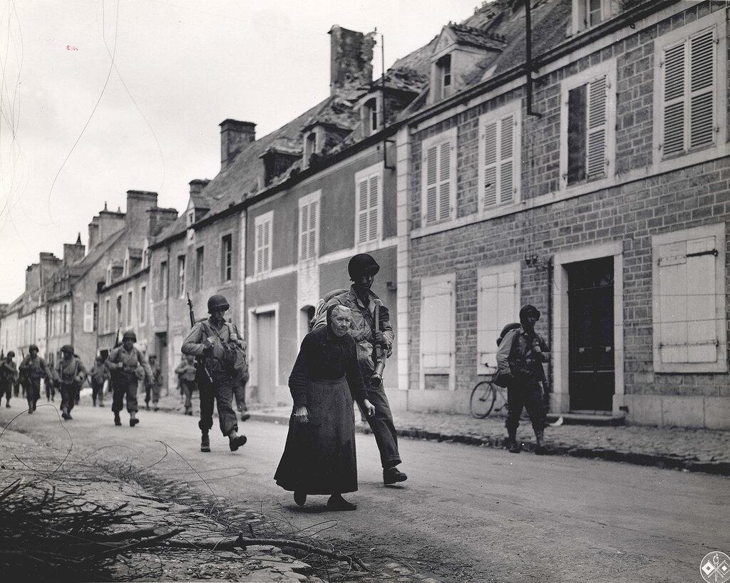 Collection Rodger Hamilton: The War Photoshttp://wosu.org/2012/archive/hamilton/gallery.php?page=gallery1Refugees leaving town.Dans une rue dont les immeubles ont peu soufferts (seules les toitures sont abimées), une vieille femme et une double co