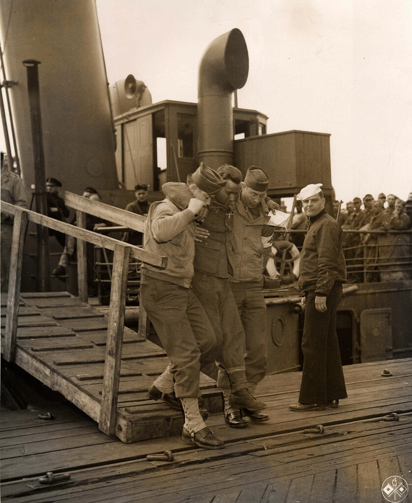 Collection Rodger Hamilton: The War Photoshttp://wosu.org/2012/archive/hamilton/gallery.php?page=gallery1Two U.S. soldiers helping a wounded German from a ship.Au pied d'une passerelle maritime deux GI' soutiennent un prisonnier allemand blessé so