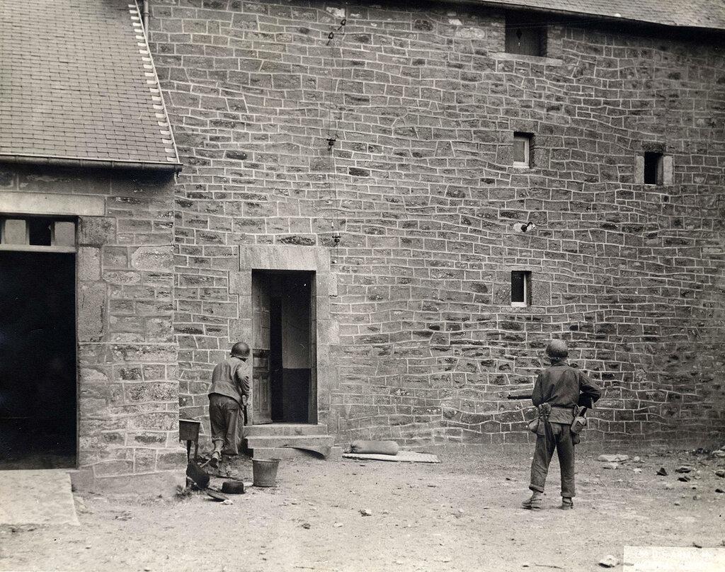 Collection Rodger Hamilton: The War Photoshttp://wosu.org/2012/archive/hamilton/gallery.php?page=gallery1Checking for snipers.Devant un bâtiment en pierres intact dont la porte est ouverte, deux soldats américains l'arme à la main.