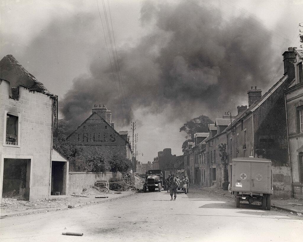 Collection Rodger Hamilton: The War Photoshttp://wosu.org/2012/archive/hamilton/gallery.php?page=gallery1Le 14 juin.Un nuage de fumée s'élève dans le ciel provenant d'immeubles incendiés par des bombardements à Carentan. A gauche, maison avec la cha