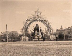 Вид одной из арок, украшенной флагами, бюстами императора и императрицы, иллюминацией, установленной на одной из [площадей] города.