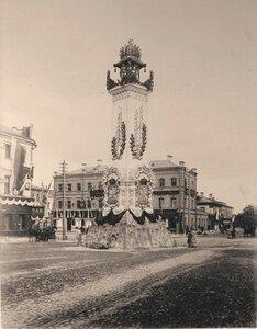 Вид одной из двух украшенных цветами, флагами, иллюминацией к торжествам коронации колонн (высотой 49 футов, увенчанной изображением императорской короны), установленной на углу Мясницкого проезда и Мясницкой улицы