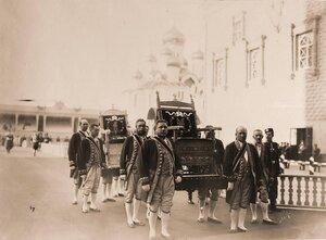 Дворцовые служащие переносят троны из [Оружейной палаты в Успенский собор] в дни подготовки к торжественной коронации.